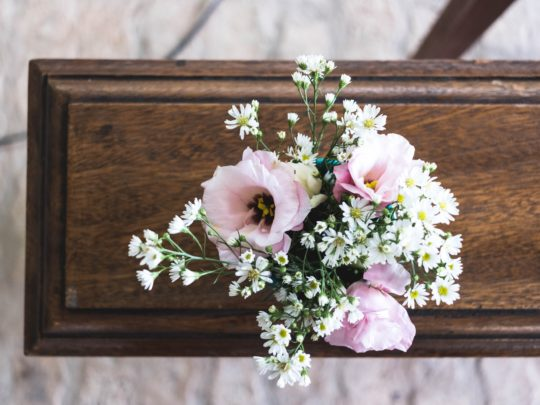 A casket topped with a flower arrangement representing the funeral services offered by Funeralocity in New Orleans, LA