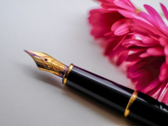 A fountain pen next to a flower that represents obituary advice from funeral comparison website Funeralocity in New Orleans, LA